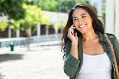 Young latin woman talking on mobile phone and looking away. Successful girl in casual calling on sma poster