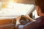 Rear view of young man looking straight while driving a car. Business man driving on the road. Back  poster