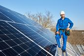 Smiling Engineer In Blue Suit And Protective Helmet Installing Solar Photovoltaic Panel System Using poster