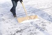 foto of snow shovel  - Shoveling snow with wooden shovel from ice for speed ice skating with wooden shovel - JPG