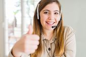 Beautiful young operator woman wearing headset at the office doing happy thumbs up gesture with hand poster