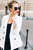Portrait Pretty Woman In Sunglasses With Red Lips On Street . She Wears White Jacket, Looking To Sid poster