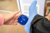 Woman With Plantar Fasciitis Uses A Spiky Ball To Massage Her Aching Foot poster