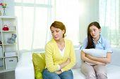 Foto da mulher ofendida, sentado no sofá com a filha adolescente ser desculpa para o que ela fez