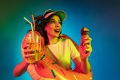 Happy Young Woman In A Rubber Ring With An Icecream And Drink On Trendy Blue Neon Studio Background. poster