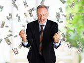 Hombre feliz disfrutando de una lluvia de dinero