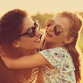 Happy Fashion Laughing Kid Girl Embracing Her Mother With Strong Love In Trendy Sunglasses Smiling A poster