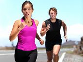 Runners - couple running training for marathon. Sport woman & man jogging on road outside. Athletic