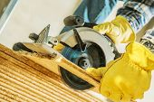 Construction Site Power Tools. Worker Cutting Plywood Using Circular Saw. Industrial Concept. poster