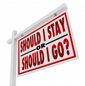 A white, wooden house for sale sign with the question Should I Stay or Should I Go, representing the