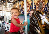 Cute mixed race little boy enjoying a ride on a fun carnival carousel. A happy boy Smiling and havin poster