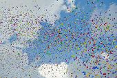Colorful confetti flying through the air against blue sky