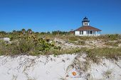 stock photo of sea oats  - The Port Boca Grande Lighthouse on Gasparilla Island Florida viewed from the sand dunes with sea oats  - JPG