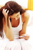image of teen pregnancy  - Beautiful young woman in the bedroom worrying because of the pregnancy test result - JPG