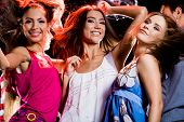 stock photo of night-club  - Three glamorous girls having fun at disco in night club - JPG