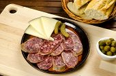 Homelike appetizer with salami, bread, olives, cheese, pickles and red wine