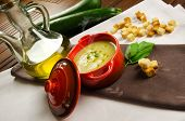 Cream of zucchini in a little casserole with croutons, oil and fresh vegetables