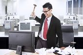 stock photo of irritated  - Angry businessman is about to throw a hammer at his computer in the office - JPG