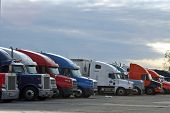 stock photo of 18-wheeler  - A line of 18 wheel big rig semi trucks parked side by side in a over night truck stop fashion no obvious logos or color scemes very genreric against a sun set sky - JPG