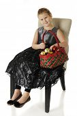 A happy elementary girl sitting in a dressy black dress while holding a red and green basket filled