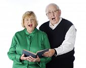 A senior adult couple singing praises together from a hymnal.  On a white background.