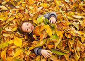 Little Girl Playing With Autumn Leaves