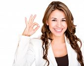 Happy businesswoman making an ok sign - isolated over a white background