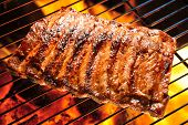 stock photo of flames  - Grilled pork ribs on the flaming grill - JPG