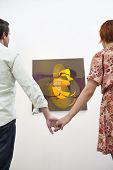 Married couple holding hands in front of painting in art gallery