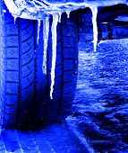 Snowy winter road with tire tracks in snow and tire and icicles