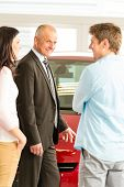 Portrait of car dealer talking with customers