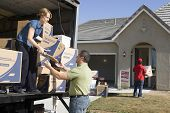 Couple unloading moving boxes from truck into new house