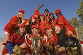 Low angle portrait of successful female softball team and coach with trophy celebrating against blue