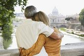 Rear view of middle aged couple on bridge looking at view of cathedral in Rome; Italy