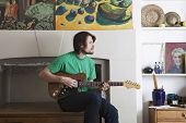 Young man playing electric guitar in the living room