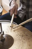 Detail shot of drumsticks on metal cymbal