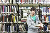 Portrait of a young male university student against bookshelf in library