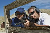 Instructor with man aiming machine gun at firing range