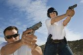 stock photo of shooting-range  - Man and woman aiming hand guns at firing range - JPG