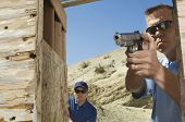 Man watching colleague aiming hand gun at firing range