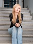 Sexy Woman Wearing Blue Jeans Sitting On A Stairs
