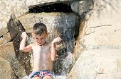 Happy Boy splashing in waterfall