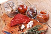 stock photo of peppercorns  - fresh raw beef meat fillet flesh with peppercorn and thyme ready to grill on wood figured old style board  over table with spices in glass - JPG