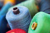 Closeup image of various colour thread rolls