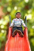 Pretty Smiling Indian Boy(kid) On Slider At A Park