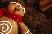Gingerbread man (ornament made of fabric to look like a cookie) on rustic, dark wood background with