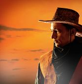 picture of west village  - American cowboy in brown hat on a sunset background outdoor - JPG