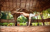 image of virabhadrasana  - Yoga virabhadrasana III warrior pose by fit man in white trousers on the drought earth in yoga shala Varkala Kerala India - JPG