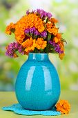 picture of marigold  - Bouquet of marigold flowers in vase on wooden table on natural background - JPG