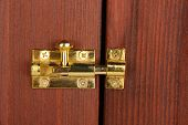 Metal latch in wooden door close-up